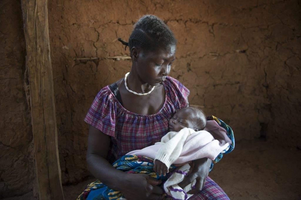 Faustina Joseph with her five month baby, born in South Sudan. The baby is sick and she has no money to go to the hospital. Philip, her husband, died in an attack 'They came to our house and ask for money - I was at the neighbour's place. When he tried to escape, he was shot right at the door, pushed inside and the door locked after him and he was burned with the house'.