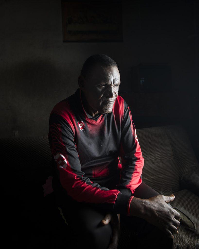 Kinshasa, République démocratique du Congo. Simon Tango, dit « Carole ». Ancien gardien de but de l'équipe nationale de football entre 1966 à 1972. Initialement appelé « les Lions », l'équipe nationale subit une défaite cuisante contre les Black stars du Ghana. Mobutu, humilié, rassemble les meilleurs joueurs congolais et reforme l'équipe nationale qu'il renomme « les Léopards ». Carole vit les premiers succès de l'équipe lors de la coupe d'Afrique des Nation (CAN) en 1968, et joue le premier match de l'équipe en tant que Zaïre, au Cameroun, en février 72. Deux ans plus tard, le Zaïre remporte la CAN organisée en Égypte. « Pendant les années Zaïre, les footballeurs ont été choyés. Aujourd'hui, les anciens joueurs sont totalement abandonnés ». Interview réalisée le 12/11/2015.Portrait posé à son domicile.