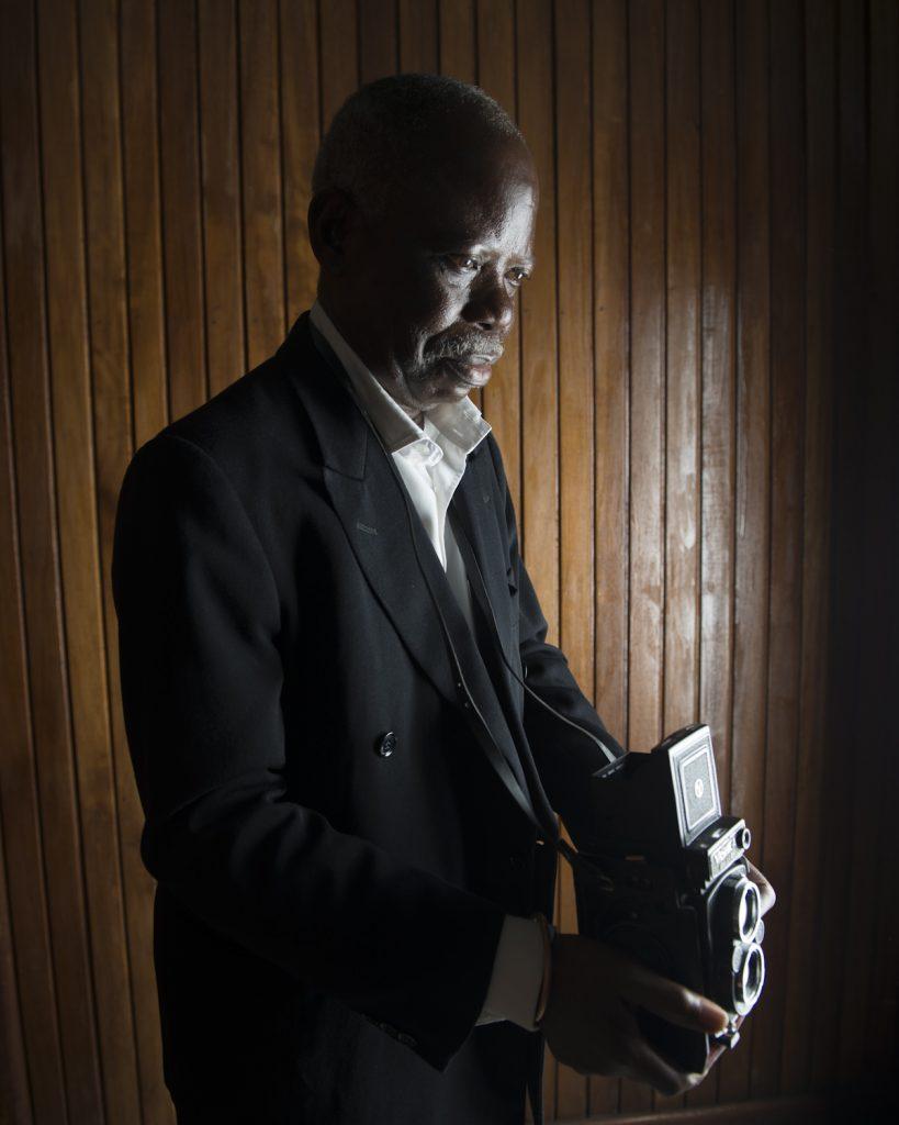 Constant, photographe, né en 1943 à Kisangani. Son père, enseignant, est passionné de photographie. Lors de son premier voyage en Europe, il ramène un appareil Kodak. Ses deux fils apprennent la photographie auprès d'Alberto, un commerçant portugais qui tient un labo à Kinshasa. Ils lancent ensemble leur premier studio, et Constant devient photographe officiel du parlement. Pendant deux décennies, il photographie les personnalités qui viennent rendre visite au Maréchal : Hailé Sélassié, Jean Paul II, Mohamed Ali, le Roi Baudouin. « Mobutu était un homme qui aimait excessivement la photographie. Il posait toujours longuement avec ses invités, pour être sûr que vous ne ratiez pas la photo ». Le 24 novembre 1990, il photographie les larmes de Mobutu lors de son discours à la nation. La sécurité tente alors d'arracher les films des photographes, mais il réussit à s'éclipser. Quand l'AFDL arrive à Kinshasa, il est obligé de se débarrasser de toutes ses archives photo, pour éviter les foudres du nouveau régime.