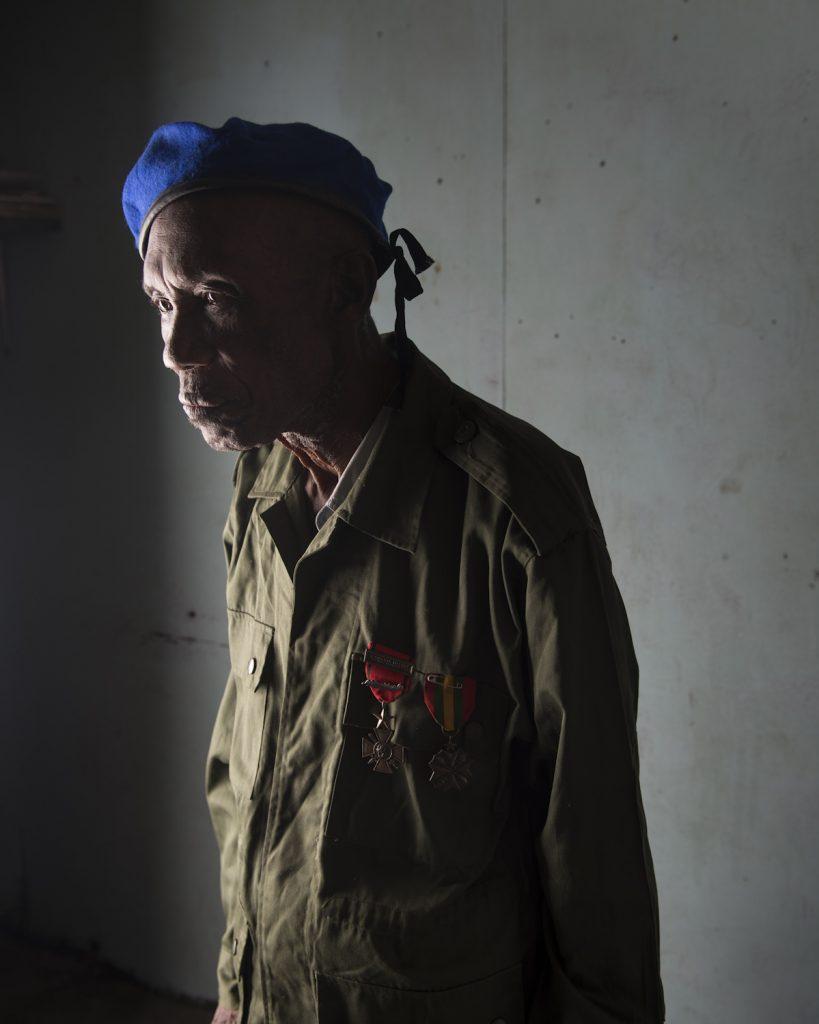 Kinshasa, République démocratique du Congo. Makengo Illenge. Né en 1936, dans la province du Bandundu. Policier formé par les Belges, il s'engage dans l'armée en 1959. Il commence ca carrière comme infirmier pour la force aérienne. En 1964, il est envoyé à Stanleyville (Kisangani) lors de la guerre contre les Simbas. Il participe ensuite à la première et à la deuxième guerre du Shaba (ancienne province du Katanga) de 1977 et 1978 lors desquelles les rebelles du FNLC (front national de libération du Congo) luttent contre Mobutu, avec le soutien de l'Angola et de Cuba. Il est ensuite envoyé à Beni, où il est nommé superviseur d'infirmerie. Il y restera trois ans avant de rejoindre sa femme et ses cinq enfants restés à Kinshasa, où il vit encore aujourd'hui. Interview réalisée le 22/11/2015.Portrait posé à son domicile.