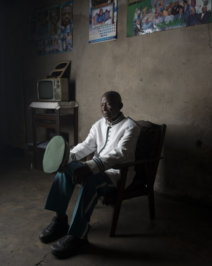Kinshasa, République démocratique du Congo. Masamba Toukala Kiese, menuisier charpentier et membre de la fanfare Kibanguiste. Né en 1931 à Mbanza Ngungu, il s'installe à Léopoldville en 1963 ; la ville est en plein boum démographique et a besoin de main d'œuvre. En 1983, Mobutu l'envoie à Mbandaka, avec une centaine d'ouvriers pour construire un palais dans la capitale de sa province natale. Masamba y restera huit mois. Le jour de l'inauguration, le président lui remit une médaille du mérite. « Mobutu était un homme bon et mauvais à la fois : si il appréciait ton travaille, il te couvrait d'argent. Mais dès que tu lui déplaisais, cela tournait très mal ».Interview réalisée le 15/11/2015Portrait posé à son domicile.