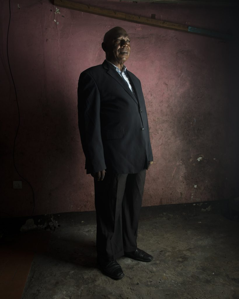 Kinshasa, République démocratique du Congo. Modeste Eboma Makundu est né à Mongbenbe en 1954 et commence sa carrière dans la jeune administration post coloniale. Proche de la famille Mobutu en Equateur, il obtient un poste dans une société allemande de fabrication de savon et d'huile. Après un court séjour en Allemagne, il s'installe à Kinshasa où il « devient » élu du MPR (Mouvement pour la Révolution) dans la commune de Kimbanseke. En 1991, lorsque Mobutu autorise le multipartisme, il crée sa propre formation, le PADER, qui ne rencontre pas un grand succès. En 2006, il s'associe avec Nzanga Mobutu et fonde l'UDEMO (Union des démocrates mobutistes), dont il est actuellement le vice-président.Interview réalisée le 27/11/2015.Portrait posé à son domicile.