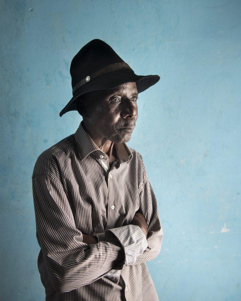 Kinshasa, République démocratique du Congo. Bikunda Buele Nzoko, dit « vieux Bikunda ». Né en 1939 à Leopoldville, de parents pêcheurs, il entame sa carrière de musicien à 14 ans, dans le groupe Watana, jouant des maracas aux cotés deDewayon et Franco. C'est ce dernier qui le pousse à devenir guitariste. Après plusieurs tournées en Europe, il fonde les Victoria Bakolo Music en 1998, à la demande de Wendo Kolosoy, star de la rumba congolaise. Le groupe, l'un des favoris de Mobutu, joue régulièrement au Palais national et à Gbadolite. Après la disparition de leur leader, les Bakolo Music continuent d'interpréter leurs classiques, tel « Marie-Louise » dans les clubs de la capitale.Interview réalisée le 10/11/2015.Portrait posé dans la salle de répétition.