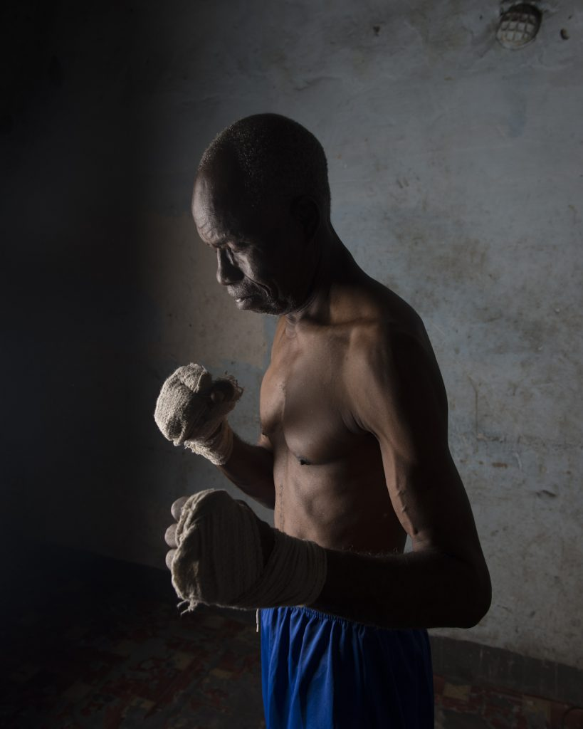 Kinshasa, République démocratique du Congo. César Sinda, ex-champion de boxe. Né en 1948, d'une famille de douze enfants, César devient boxeur après que sa sœur se fasse attaquer à l'école. Il devient champion national des poids légers, puis est couronné champion d'Afrique en Zambie. A son retour à Kinshasa, Mobutu est absent, mais laisse des ordres pour lui attribuer une maison et une voiture neuve, dont il ne verra jamais la couleur. En 1969, il est envoyé aux jeux olympiques de Mexico. Quand Mohamed Ali arrive à Kinshasa, César Sinda est au Etats-Unis, dans l'espoir d'y suivre un entrainement professionnel pour devenir champion du monde des poids légers. Parti avec six dollars en poches, un pasteur de New York le prend sous son aile et l'adopte officiellement. Après plusieurs défaites, sa carrière décolle enfin. Mais en 1978, il retourne au Congo pour enterrer son père. Quelques mois plus tard, sa sœur décède, et son passeport est volé. Il décide alors de rester à Kinshasa, et devient entraineur. Il sera couronné de l'ordre du Léopard par Mobutu.Interview réalisée le 21/11/2015.Portrait posé à son domicile.