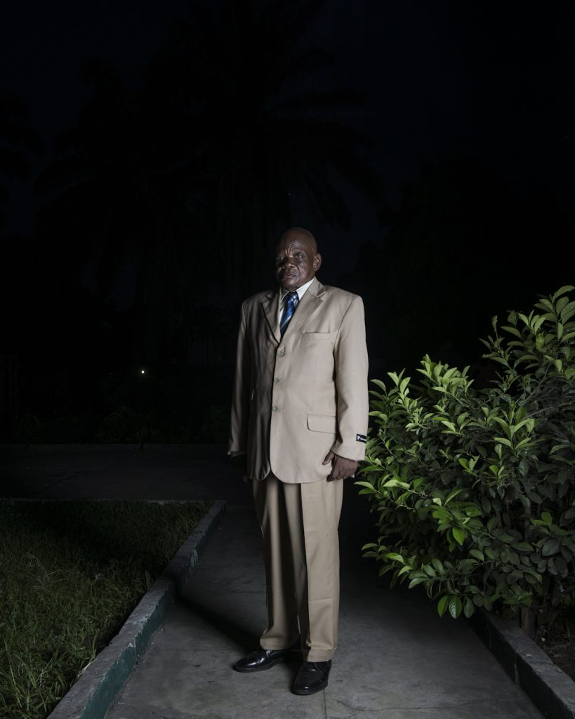 Kinshasa, République démocratique du Congo. Honoré Augustin Kabala Mwanbay. Né en 1942 au Kasaï occidental. Agent à la Société minière de Bakwanga ( MIBA), active dans l'exploitation du diamant. Dès les années septante, la MIBA subit de plein fouet la gestion de Mobutu, qui puise dans les recettes de la société pour assouvir ses ambitions personnelles. Honoré Augustin, qui a suivit une formation pastoral en 1964 devient alors Révérant, et s'installe à Kinshasa. Il rejoint le mouvement religieux Kimbanguiste, en plein essort depuis sa reconnaissance par le pouvoir en place. Il restera jusqu'à aujourd'hui. Il garde un bon souvenir de l'époque Zaïroise, malgré l'inflation et la corruption.Interview réalisée le 13/11/2015.Portrait posé devant son domicile.